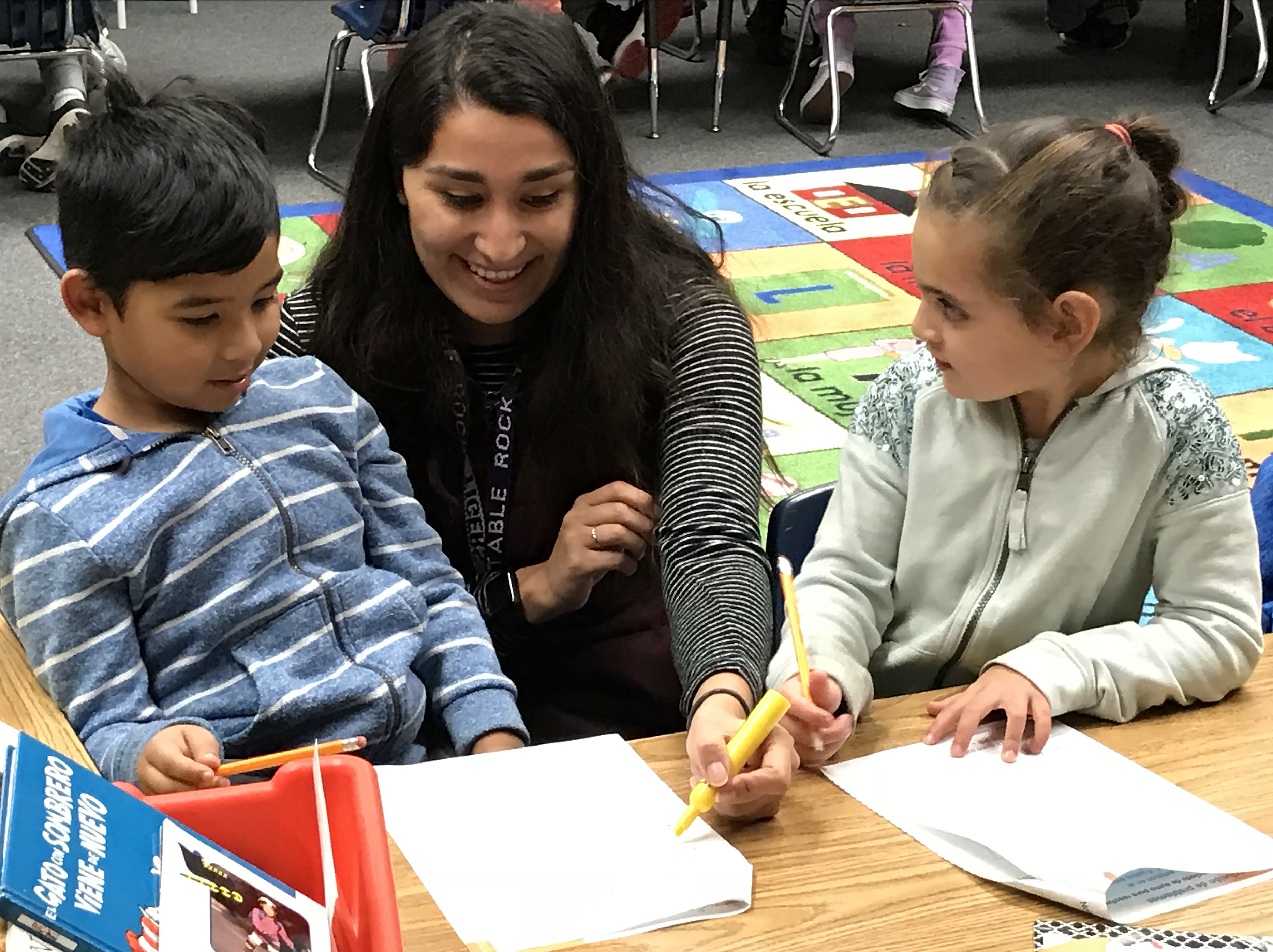Teacher working with two young students.