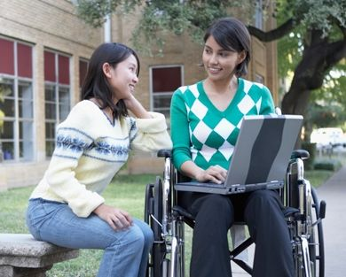 two students, one in a wheelchair showing the other student their laptop