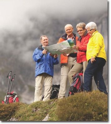 a photo of 4 hikers looking at a map together