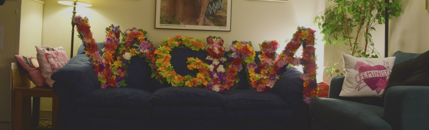"The word ""Vagina"" spelled in silk flowers, propped up on a couch in the WRC living room."